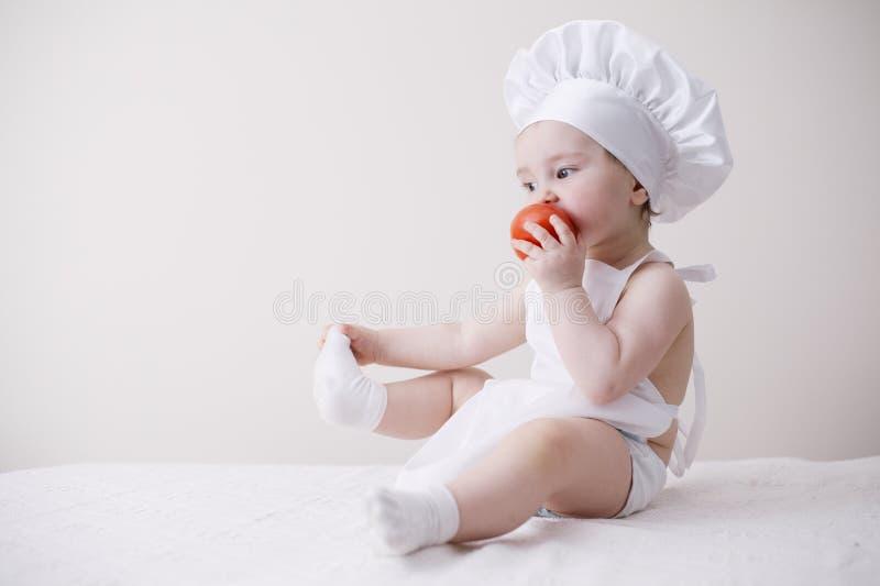 Χαριτωμένος λίγος μάγειρας τρώει την ντομάτα στοκ φωτογραφία με δικαίωμα ελεύθερης χρήσης