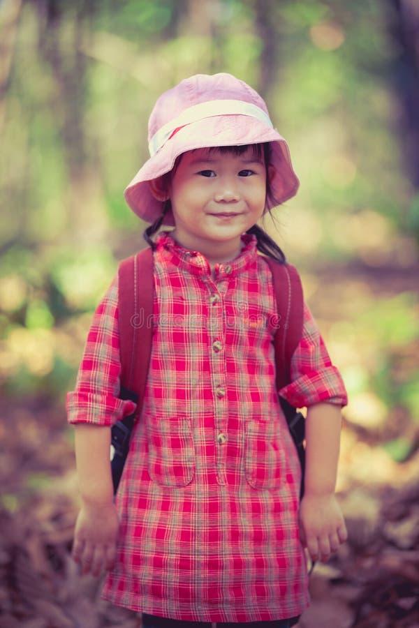 Χαριτωμένος λίγο ασιατικό κορίτσι που εξετάζει τη κάμερα και που χαμογελά πέρα από τη φύση στοκ εικόνες