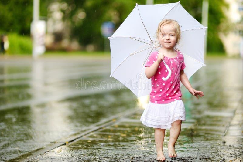 Χαριτωμένος λίγο κορίτσι μικρών παιδιών που έχει τη διασκέδαση κάτω από μια βροχή στοκ φωτογραφία