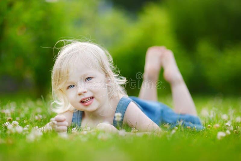 Χαριτωμένος λίγο κορίτσι μικρών παιδιών που βάζει στη χλόη στοκ εικόνα