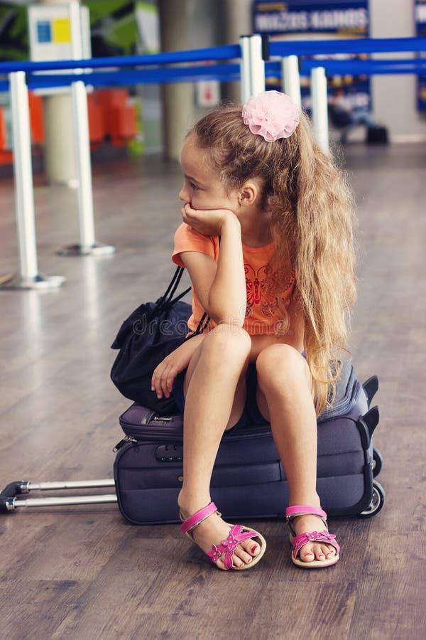 Χαριτωμένος λίγο κουρασμένο κορίτσι παιδιών στον αερολιμένα, ταξίδι παιδί λυπημένο στοκ φωτογραφία