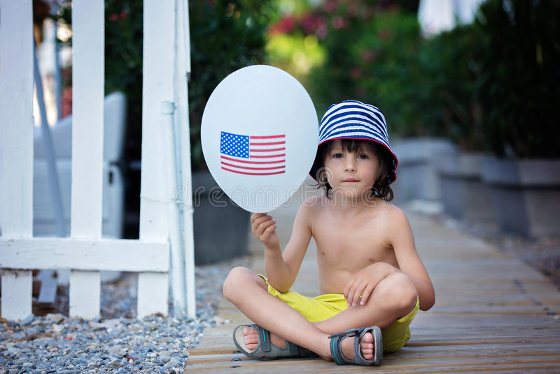 Χαριτωμένος λίγο παιδί, αγόρι, που παίζει με το μπαλόνι με την ΑΜΕΡΙΚΑΝΙΚΗ σημαία στοκ φωτογραφία