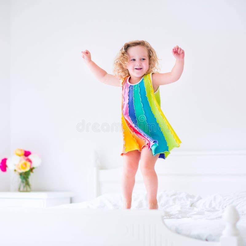 Χαριτωμένος λίγο σγουρό κορίτσι μικρών παιδιών που πηδά στο άσπρο κρεβάτι στοκ φωτογραφίες