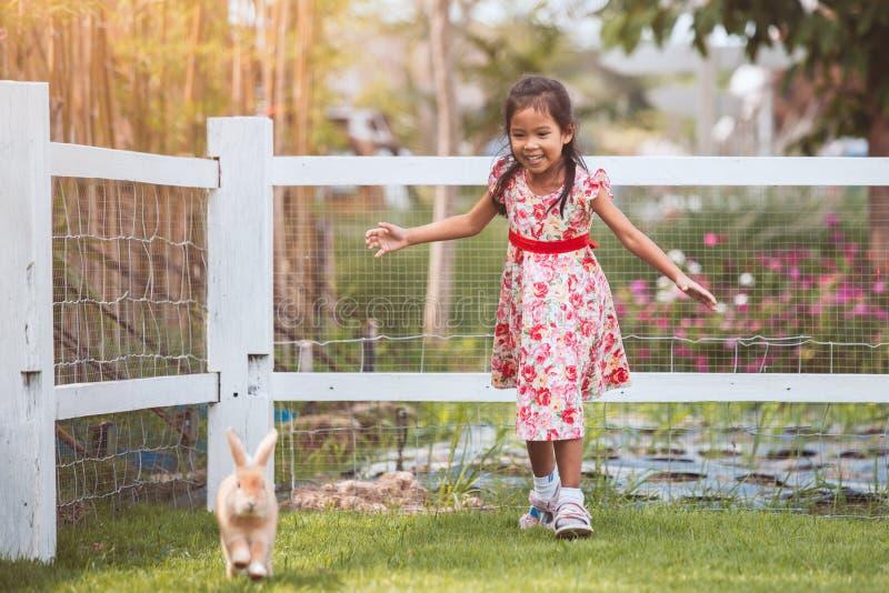 Χαριτωμένος Ασιάτης λίγο κορίτσι παιδιών που τρέχει για να πιάσει ένα κουνέλι με τη διασκέδαση στοκ φωτογραφία