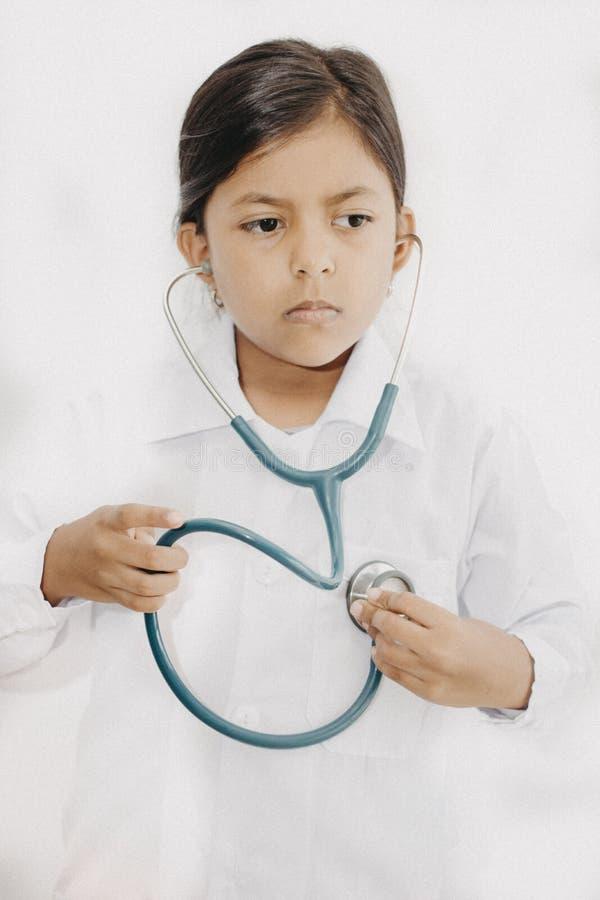 Χαριτωμένος γιατρός μικρών κοριτσιών με ομοιόμορφο στοκ εικόνα