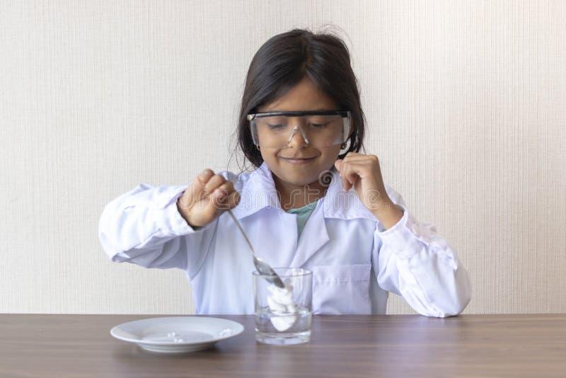 Χαριτωμένος επιστήμονας μικρών κοριτσιών που πραγματοποιεί ένα πείραμα στοκ εικόνες