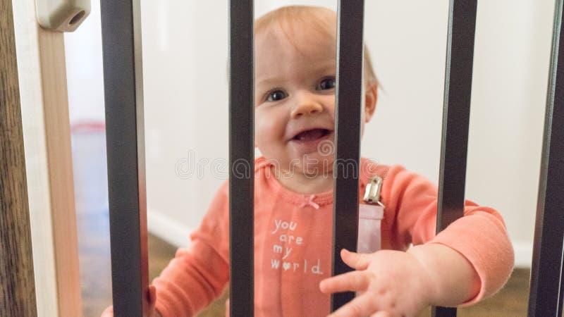 Χαριτωμένος ευτυχής λίγο μωρό που κοιτάζει αδιάκριτα μέσω των ραγών στοκ εικόνα με δικαίωμα ελεύθερης χρήσης