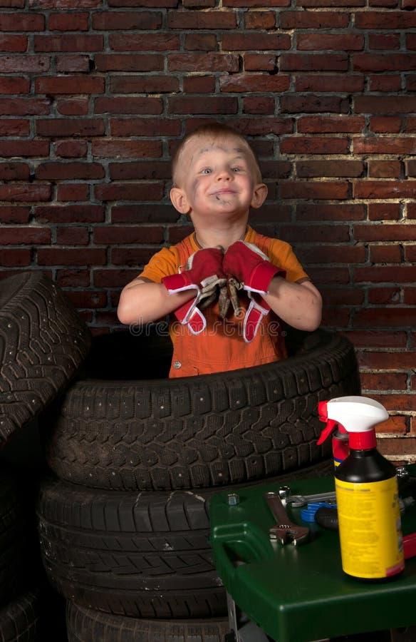 Χαριτωμένος και αστείος λίγος μηχανικός με μια ρόδα στοκ εικόνες