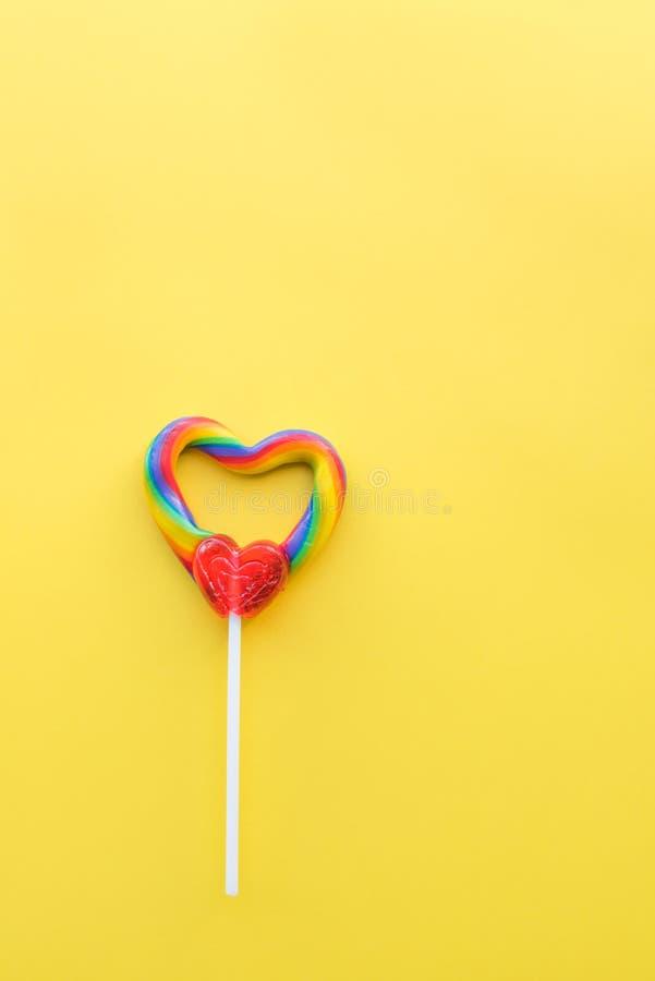 Χαριτωμένος καρδιά-διαμορφωμένος στρόβιλος ουράνιων τόξων lollipop στο στερεό κίτρινο σχήμα πορτρέτου υποβάθρου στοκ φωτογραφία