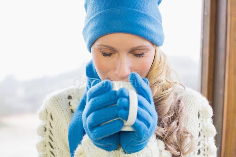Χαριτωμένος καφές κατανάλωσης γυναικών στο θερμό ιματισμό στοκ εικόνες