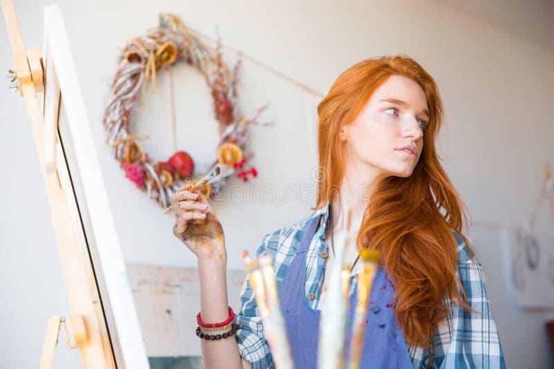 Χαριτωμένος καλός νέος ζωγράφος γυναικών που εργάζεται στο εργαστήριο τέχνης στοκ φωτογραφίες