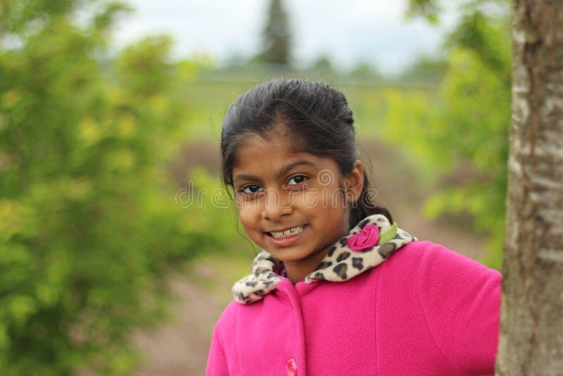 Χαριτωμένος κορμός δέντρων εκμετάλλευσης κοριτσιών στοκ εικόνες