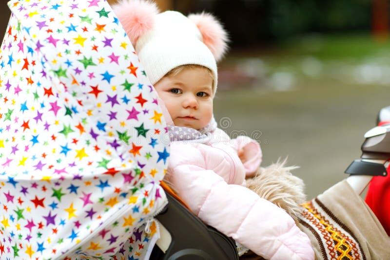 Χαριτωμένος λίγη όμορφη συνεδρίαση κοριτσάκι στο καροτσάκι ή τον περιπατητή την κρύα ημέρα στοκ εικόνες
