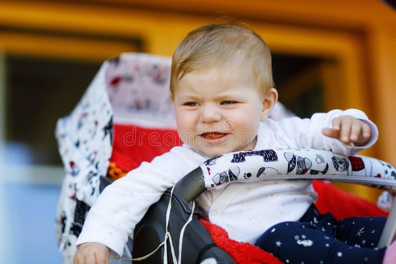 Χαριτωμένος λίγη όμορφη συνεδρίαση κοριτσάκι στο καροτσάκι ή τον περιπατητή και αναμονή για το mom Φωνάζοντας λυπημένο παιδί με τ στοκ φωτογραφία