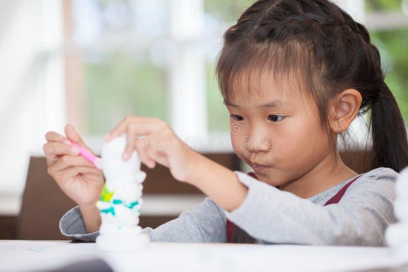 Χαριτωμένος λίγος ασιατικός σπουδαστής κοριτσιών που χρωματίζει ένα κεραμικό πρότυπο αγγειοπλαστικής στο σχολείο τάξεων καλλιτέχν στοκ φωτογραφία