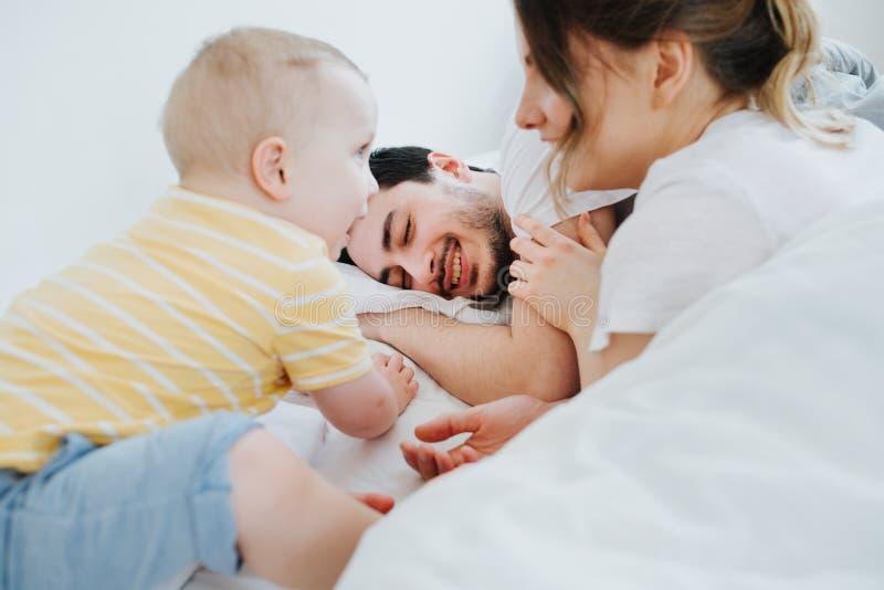Χαριτωμένος λίγος γιος μαζί με τη μητέρα του προσπαθεί ξυπνήστε στον πατέρα του στοκ φωτογραφία με δικαίωμα ελεύθερης χρήσης