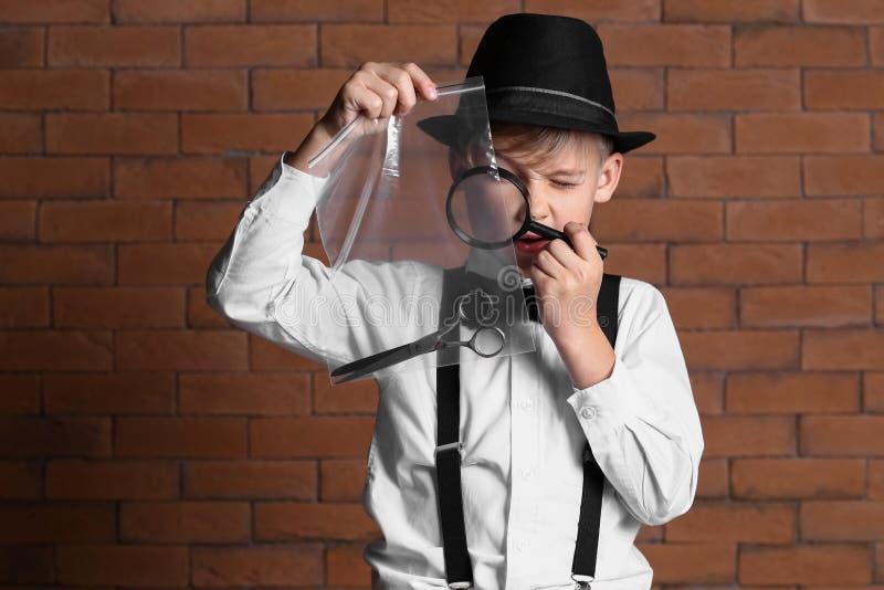 Χαριτωμένος λίγος ιδιωτικός αστυνομικός με τα στοιχεία ενάντια στο τουβλότοιχο στοκ φωτογραφία με δικαίωμα ελεύθερης χρήσης