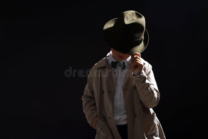 Χαριτωμένος λίγος ιδιωτικός αστυνομικός στο σκοτεινό υπόβαθρο στοκ εικόνες