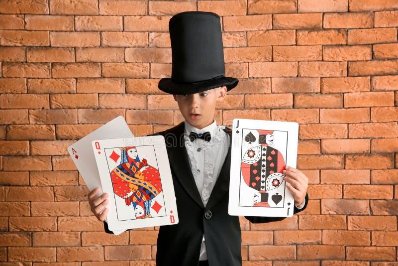 Χαριτωμένος λίγος μάγος με τις κάρτες ενάντια στο τουβλότοιχο στοκ φωτογραφία με δικαίωμα ελεύθερης χρήσης