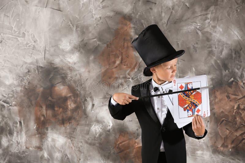 Χαριτωμένος λίγος μάγος που παρουσιάζει τέχνασμα με τις κάρτες στο υπόβαθρο grunge στοκ φωτογραφίες με δικαίωμα ελεύθερης χρήσης