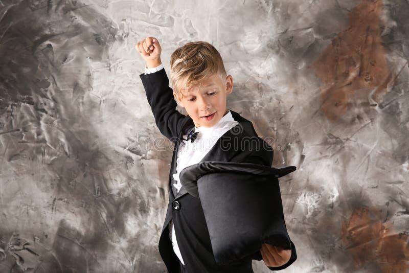 Χαριτωμένος λίγος μάγος που παρουσιάζει τέχνασμα με το καπέλο στο υπόβαθρο grunge στοκ φωτογραφία με δικαίωμα ελεύθερης χρήσης