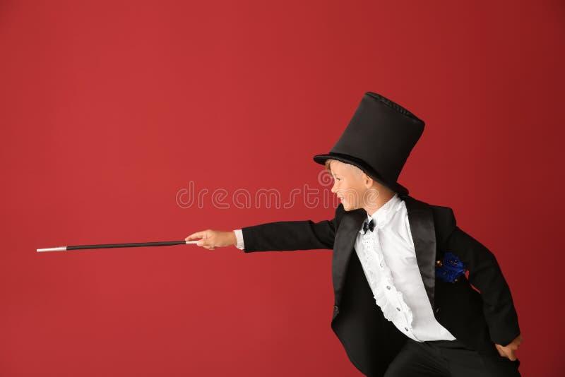 Χαριτωμένος λίγος μάγος που παρουσιάζει τεχνάσματα στο υπόβαθρο χρώματος στοκ φωτογραφία με δικαίωμα ελεύθερης χρήσης