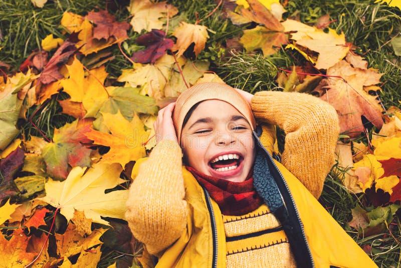 Χαριτωμένος λίγο αγόρι παιδιών που έχει τη διασκέδαση στο πάρκο φθινοπώρου στοκ φωτογραφία