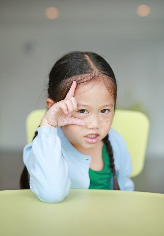 Χαριτωμένος λίγο ασιατικό κορίτσι παιδιών που βάζει στον πίνακα παιδιών με την εξέταση τη κάμερα στοκ εικόνα