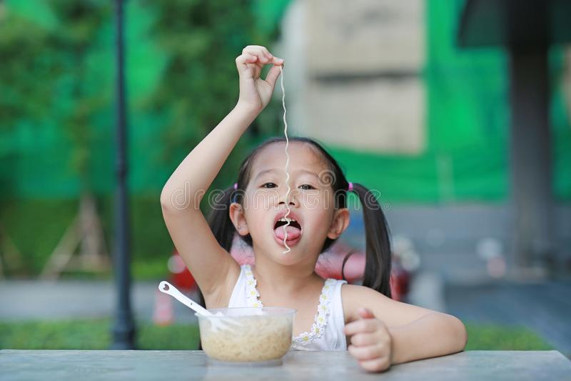 Χαριτωμένος λίγο ασιατικό κορίτσι παιδιών που τρώει τα στιγμιαία νουντλς στον πίνακα στοκ εικόνες με δικαίωμα ελεύθερης χρήσης