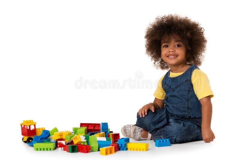 Χαριτωμένος λίγο κορίτσι αφροαμερικάνων που παίζει με τα μέρη των ζωηρόχρωμων πλαστικών φραγμών εσωτερικών απομονωμένος στοκ εικόνα