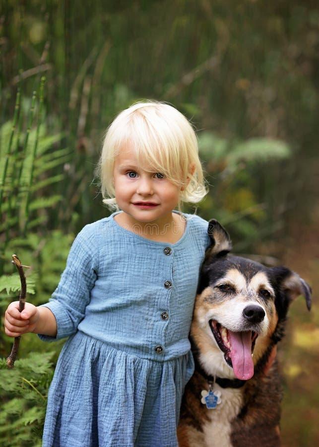 Χαριτωμένος λίγο κορίτσι μικρών παιδιών που παίζει έξω με το σκυλί της Pet της στοκ φωτογραφίες