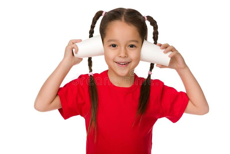 Χαριτωμένος λίγο κορίτσι παιδιών που παίζει με τα φλυτζάνια εγγράφου στοκ φωτογραφίες