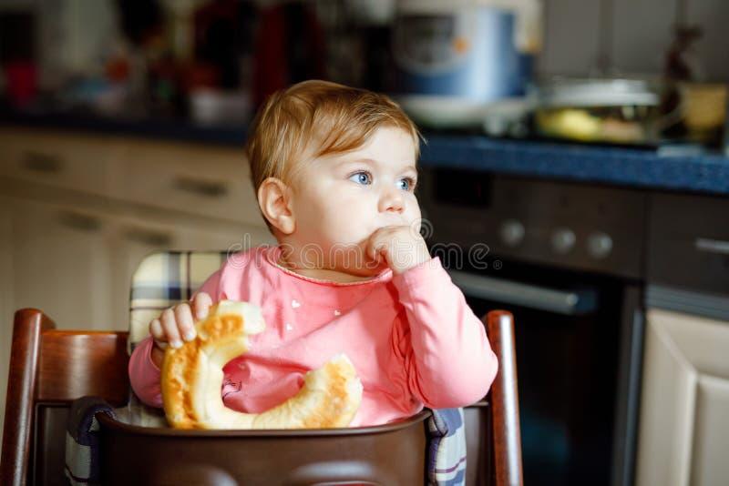 Χαριτωμένος λίγο κοριτσάκι που τρώει το ψωμί Λατρευτό παιδί που τρώει για πρώτη φορά το κομμάτι pretzel ή croissant : στοκ εικόνα με δικαίωμα ελεύθερης χρήσης