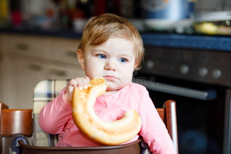 Χαριτωμένος λίγο κοριτσάκι που τρώει το ψωμί Λατρευτό παιδί που τρώει για πρώτη φορά το κομμάτι pretzel ή croissant : στοκ φωτογραφίες με δικαίωμα ελεύθερης χρήσης