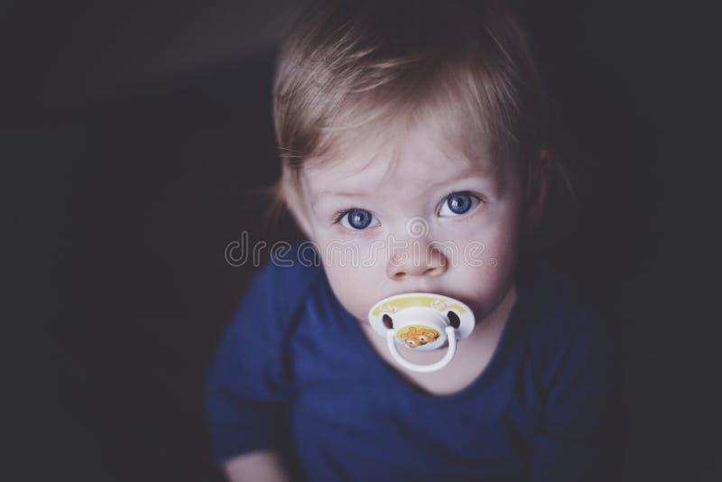 Χαριτωμένος λίγο μωρό με τα μπλε μάτια με μια θηλή στο στόμα της που ανατρέχει στοκ εικόνες