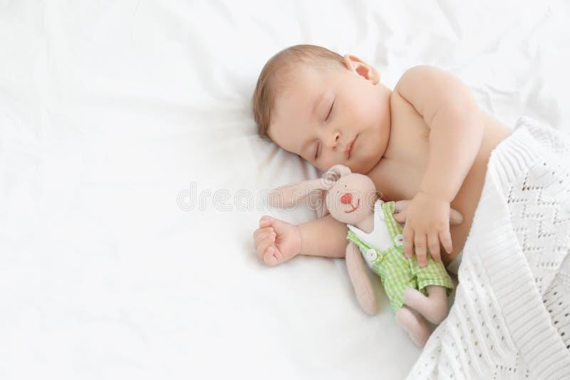Χαριτωμένος λίγο μωρό με τον ύπνο παιχνιδιών στο κρεβάτι στοκ εικόνες