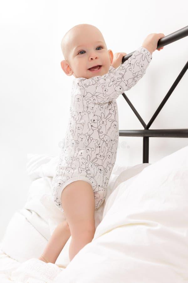 Χαριτωμένος λίγο χαμογελώντας νήπιο αγοράκι που στέκεται στο κρεβάτι γονέων ` s, που κρατά επάνω headboard Πρώτες προσπάθειες να  στοκ φωτογραφίες
