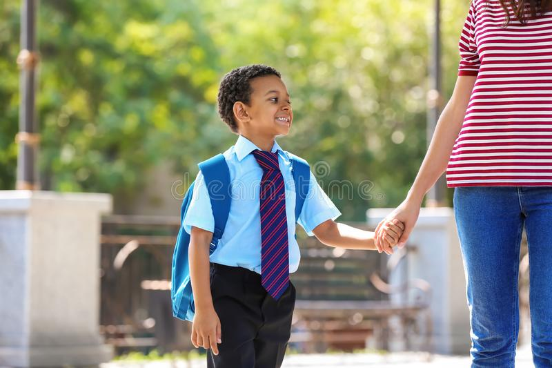Χαριτωμένος μαθητής αφροαμερικάνων που πηγαίνει στο σχολείο με τη μητέρα στοκ εικόνες