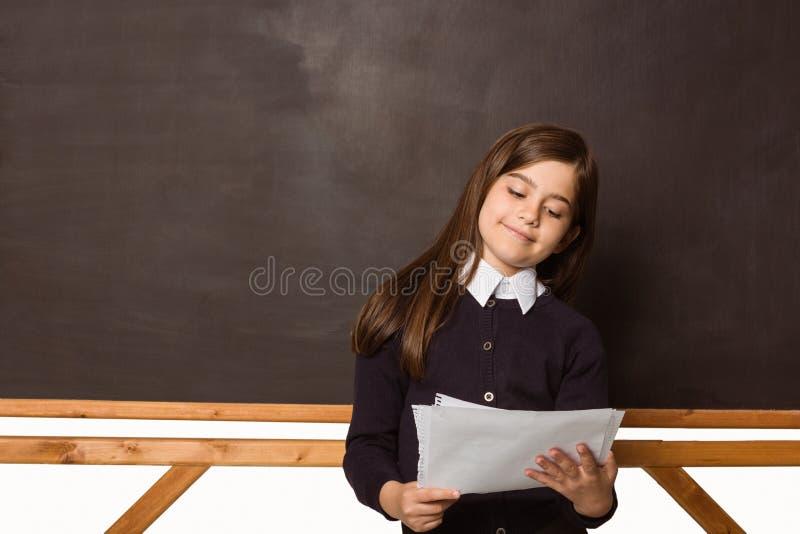 Χαριτωμένος μαθητής που κρατά τις άσπρες σελίδες στοκ εικόνες