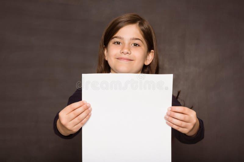 Χαριτωμένος μαθητής που παρουσιάζει άσπρη σελίδα στοκ φωτογραφία με δικαίωμα ελεύθερης χρήσης