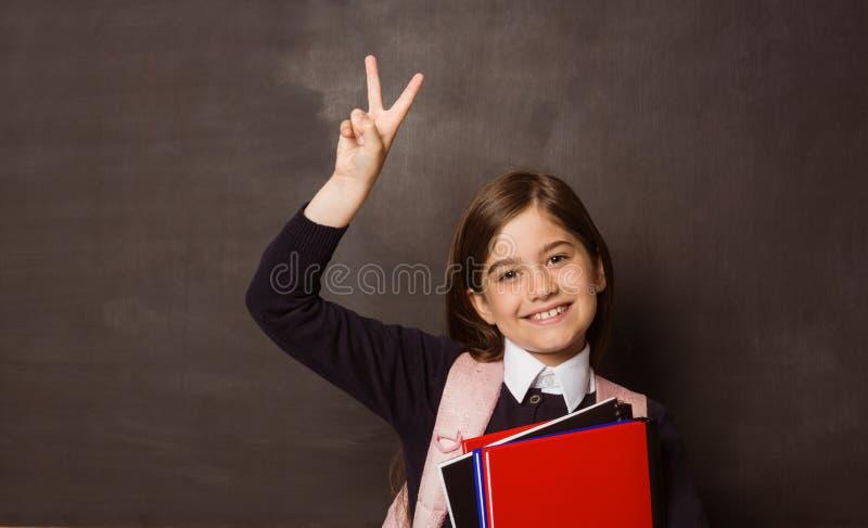 Χαριτωμένος μαθητής που χαμογελά στα βιβλία εκμετάλλευσης καμερών στοκ εικόνες