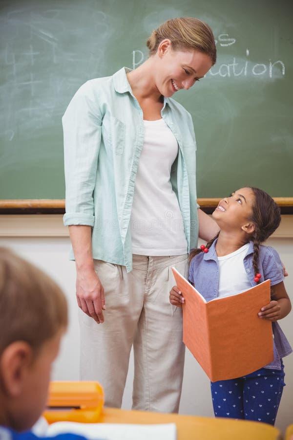 Χαριτωμένος μαθητής που χαμογελά στο δάσκαλό της κατά τη διάρκεια της παρουσίασης κατηγορίας στοκ εικόνες