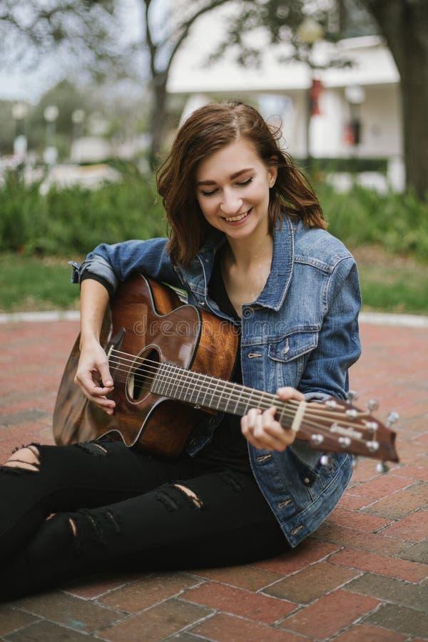 Χαριτωμένος νέος θηλυκός μουσικός που διαμορφώνει και που χαμογελά για τη κάμερα έξω στοκ φωτογραφία με δικαίωμα ελεύθερης χρήσης