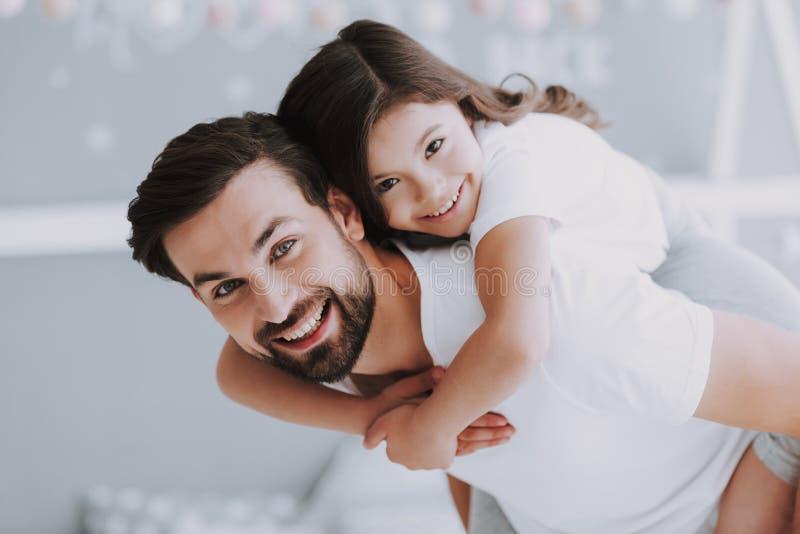 Χαριτωμένος νέος στη πλάτη γύρος κορών με τον μπαμπά στοκ εικόνες με δικαίωμα ελεύθερης χρήσης
