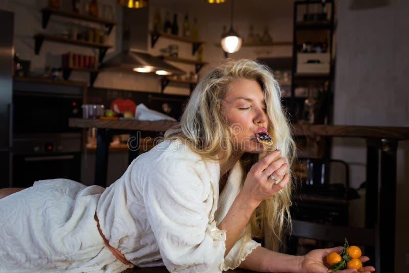 Χαριτωμένος ξανθός στο μπουρνούζι βρίσκεται στον πίνακα ενάντια στη σύγχρονη κουζίνα στοκ φωτογραφία με δικαίωμα ελεύθερης χρήσης