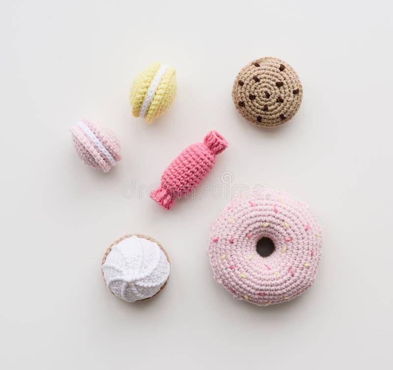 Χαριτωμένος πλέξτε τα παιχνίδια για τα παιδιά Μπισκότα, macarons, μιμήσεις καραμελών και doughnut στην ξύλινη τοπ άποψη υποβάθρου στοκ φωτογραφία με δικαίωμα ελεύθερης χρήσης