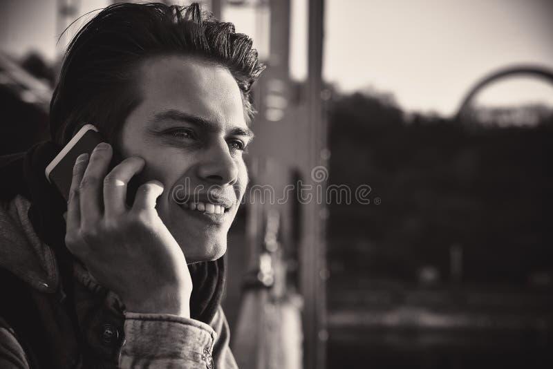 Χαριτωμένος τύπος χαμόγελου που μιλά στο τηλέφωνο που στέκεται στη νύφη στενό πορτρέτο επάνω στοκ φωτογραφία με δικαίωμα ελεύθερης χρήσης