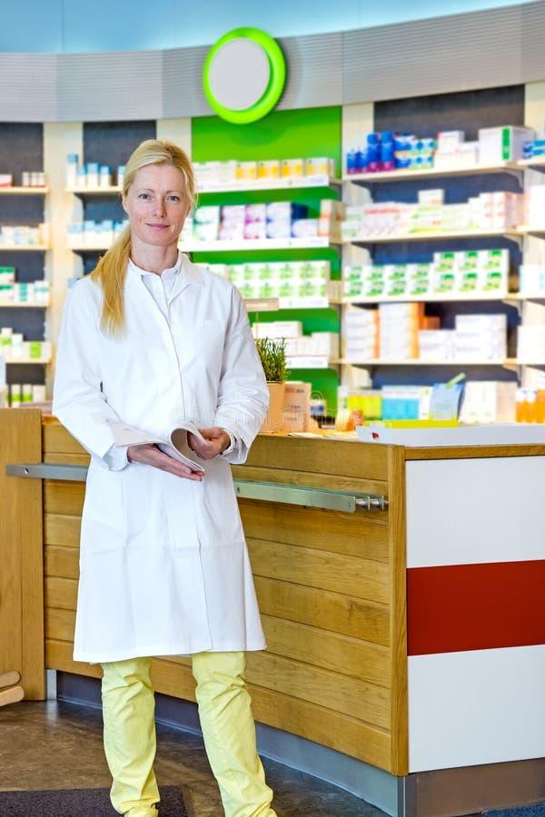Χαριτωμένος φαρμακοποιός που στέκεται κοντά στο μετρητή στοκ εικόνα με δικαίωμα ελεύθερης χρήσης