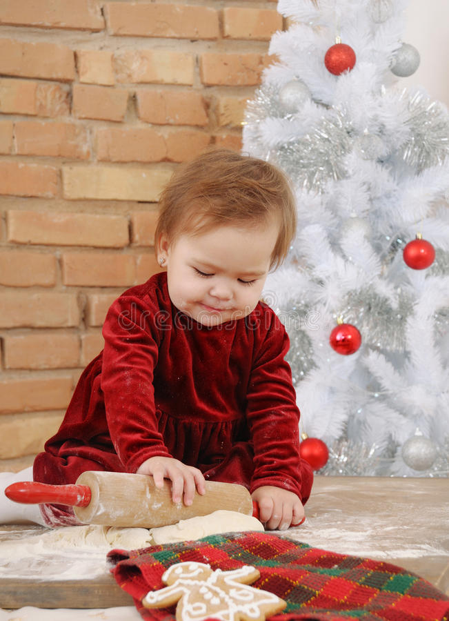 Χαριτωμένος χαμογελώντας λίγο κοριτσάκι στο κόκκινο φόρεμα που κατασκευάζει τα μπισκότα στοκ εικόνες