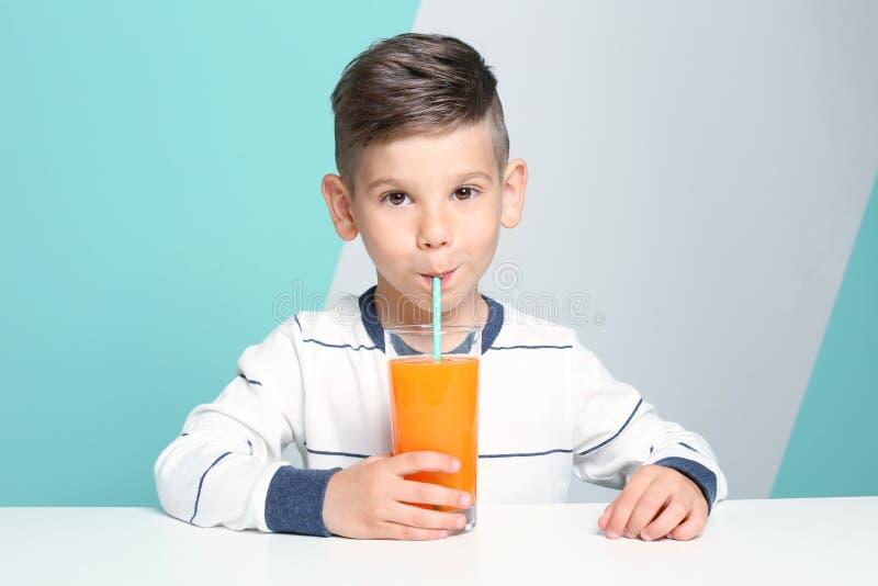 Χαριτωμένος χυμός κατανάλωσης μικρών παιδιών καθμένος στον πίνακα στοκ εικόνες